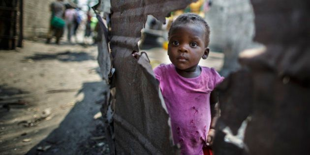 Beira, Mozambique - September 28: A little girl stands behind a broken wall in a slum in the urban area...