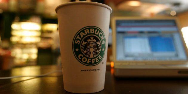 A coffee cup sits next to a laptop connected to the Internet using a Wi-Fi modem at a Starbucks coffee...