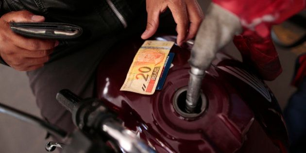 A gas station employee refuels a motorcycle in Brasilia November 7, 2014. State-run Brazilian oil producer...