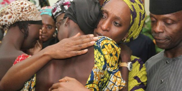 Nigerian Vice President Yemi Osinbajo (R) looks on while his wife Dolapo (C) comforts one of the 21 freed...