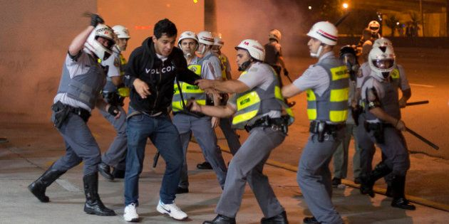 A student is detained after clashes with police broke out after the end a peaceful anti-government demonstration,...