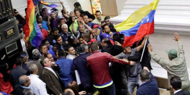 Supporters of Venezuela's President Nicolas Maduro storm into in a session of the National Assembly in...
