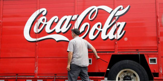 A delivery man closes the compartments on a Coca-Cola truck, Thursday, July 9, 2015, in Haverhill, Mass....