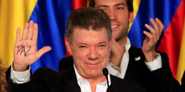 Colombian presidential candidate and President Juan Manuel Santos celebrates, holding up his right hand,...