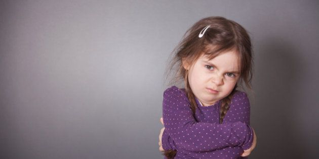 A little cute Girl is sulking. She is wearing a purple shirt in front of a gray