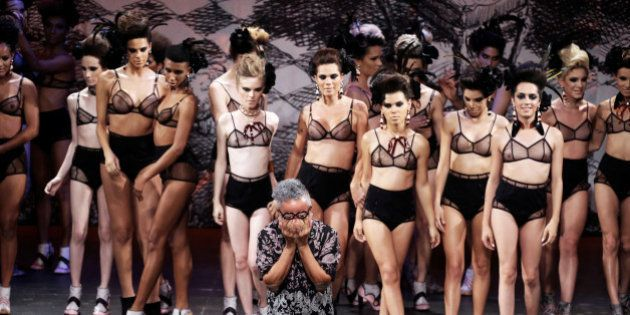 Brazilian designer Ronaldo Fraga reacts next to transsexual models at the end of the presentation of...