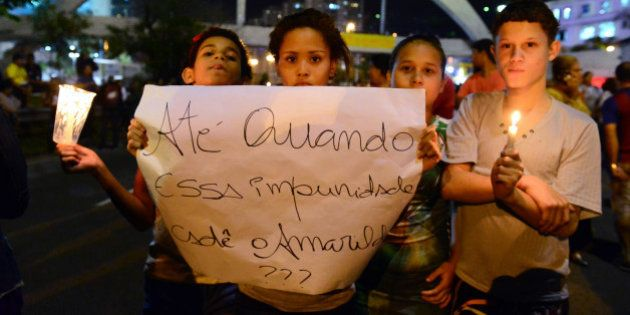 Boys and girls protesting against police repression block a road near the biggest shantytown in Rio de...
