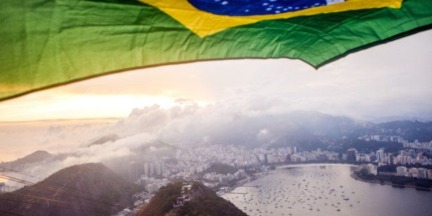 A colorful brazilian flag flying over the top of Rio De Janeiro in Brazil at