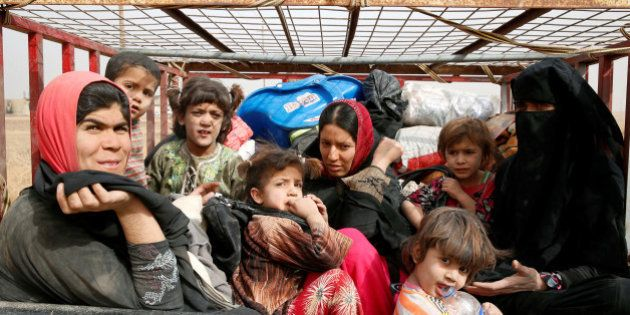 Displaced Iraqi women and children sit at the back of a vehicle after escaping from Islamic State controlled...