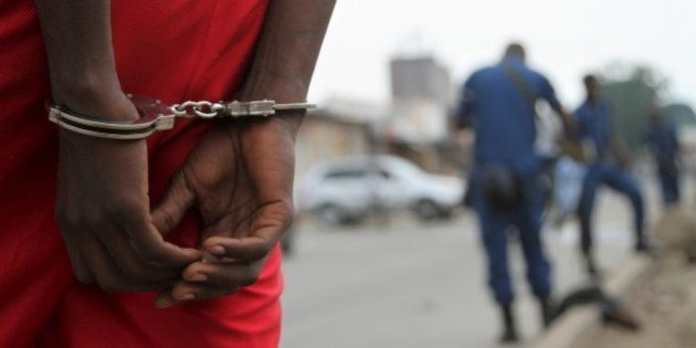 A suspect is handcuffed and detained by policemen after a grenade attack of Burundi's capital Bujumbura,...