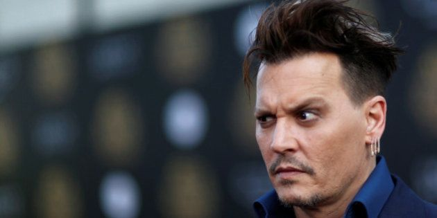 Cast member Johnny Depp poses at the premiere