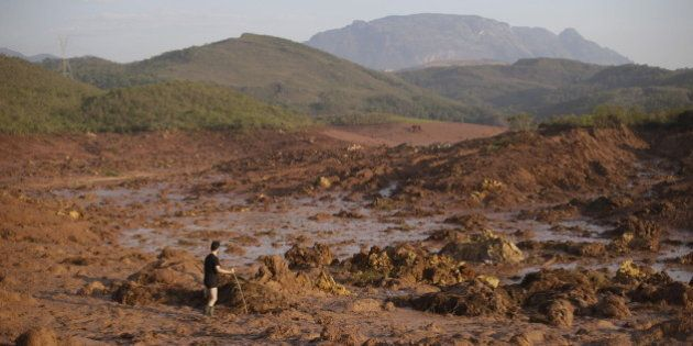A man walks following a mudslide after a dam owned by Vale SA and BHP Billiton Ltd burst in Mariana,...