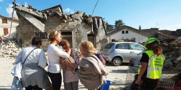 Women cry in front of damaged houses in a street in the central Italian village of Illica, near Accumoli,...