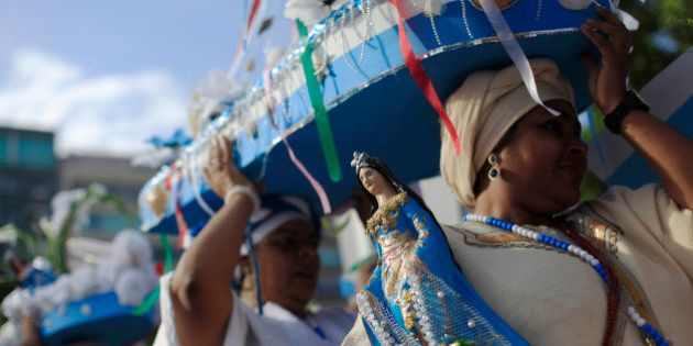 Followers of the Afro-Brazilian religion Umbanda carry offerings and an image of Iemanja, goddess of...