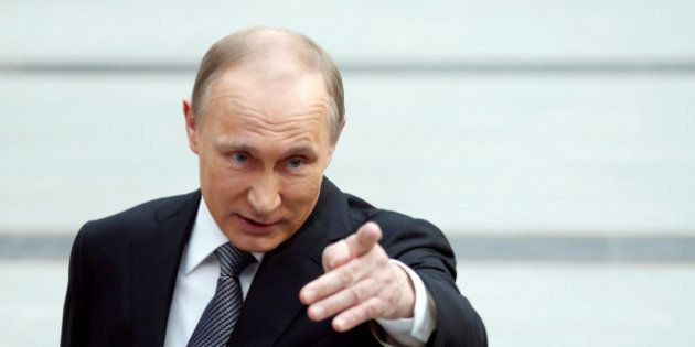 Russian President Vladimir Putin gestures as he speaks during a meeting with journalists after a live...