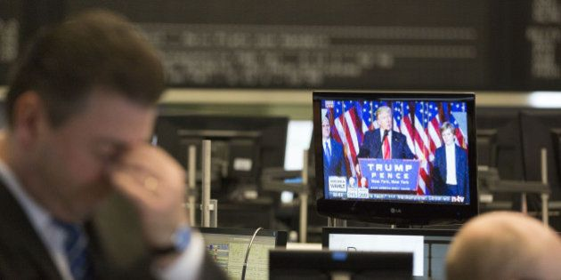 A trader reacts as a television news report shows U.S. President-elect Donald Trump speaking following...