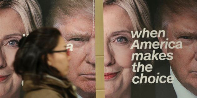 A woman walks by banners of Democratic presidential candidate Hillary Clinton and Republican presidential...