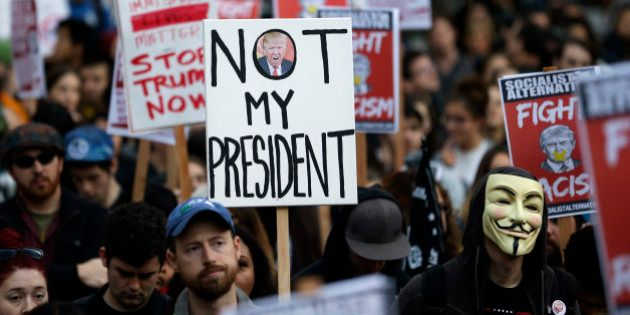 Protesters hold signs during a protest against the election of President-elect Donald Trump, Wednesday,...