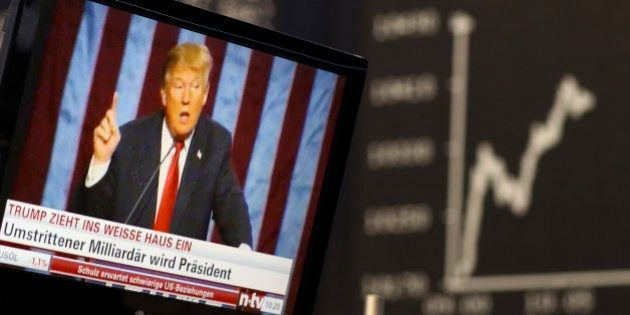 A TV screen showing U.S. President-elect Donald Trump is pictured in front of the German share price...