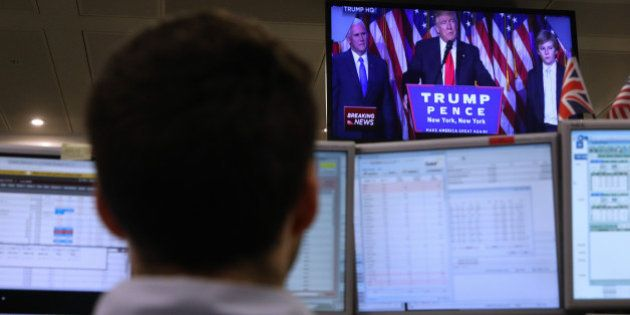 A trader watches a television screen displaying a news channel showing U.S. President-elect Donald Trump...