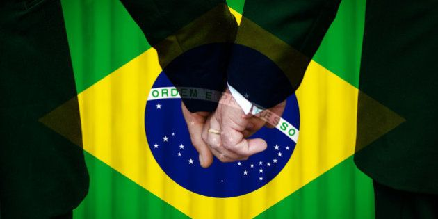 Two gay men stand hand in hand before a marriage altar featuring an overlay of the flag colors of Brazil,...