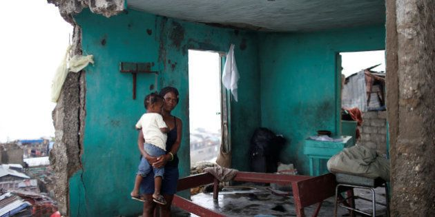 Nathalie Pierre, 28, poses for a photograph with her daughter Rose, 3, in their destroyed house after...