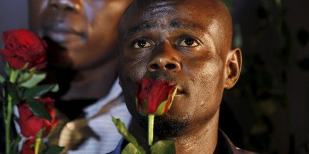 A man holds a rose as he mourns Kenyan soldiers serving in the African Union Mission in Somalia (AMISOM)...