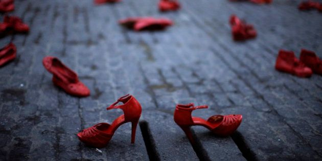 Red shoes are displayed as part of a protest highlighting violence against women at the Sant Jaume square...