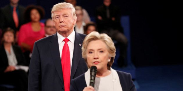 Republican U.S. presidential nominee Donald Trump listens as Democratic nominee Hillary Clinton answers...