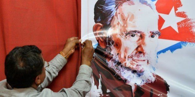 An Indian member of the Communist Party of India (Marxist) (CPI(M)), hangs an image of former Cuban President...