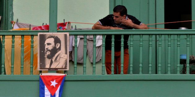 TOPSHOT - A man remains in a balcony next to a picture of Cuban revolutionary leader Fidel Castro at...