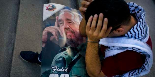 Palestinian medical student Adham Motawi, with an image of Fidel Castro, holds his head in disbelief...