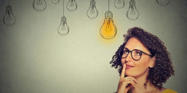 Portrait thinking woman in glasses looking up with light idea bulb above head isolated on gray wall