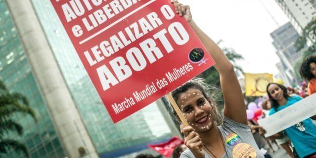 SAO PAULO, BRAZIL  MARCH 8: Girl holds a poster for legalizing abortion during the International Women's Day celebration in Sao Paulo, Brazil on March 8 , 2016. Hundreds of women protest violence against women and chant slogans in favor of abortion during the event. (Photo by Dário Oliveira/Anadolu Agency/Getty Images)