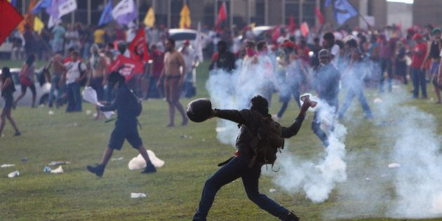 An anti-government demonstrator throws back a tear gas canister during a clash with riot policemen during...