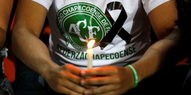A fan of Atletico Nacional soccer club holds a candle and wears a shirt in support while paying tribute...