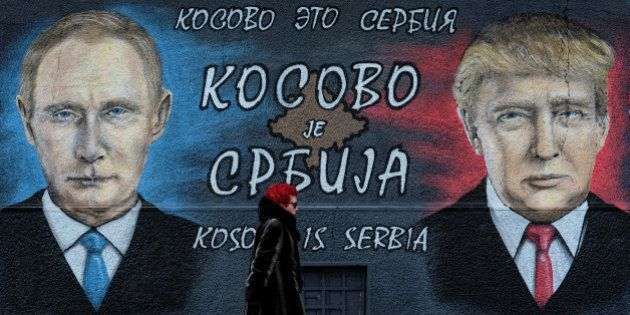 A woman walks past a mural of U.S. president-elect Donald Trump and Russian President Vladimir Putin...