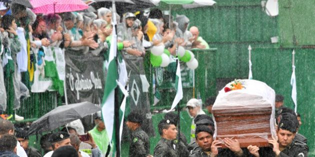Soldiers carry into the stadium under heavy rain the coffins of the members of the Chapecoense Real football...