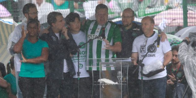 Chapeco mayor Luciano Buligon (C) gives his speech wearing a Atletico Nacional de Medelin jersey while...
