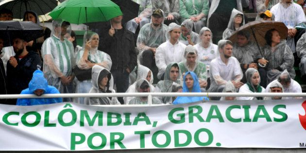 People attend under the rain the funeral of the members of the Chapecoense Real football club team killed...