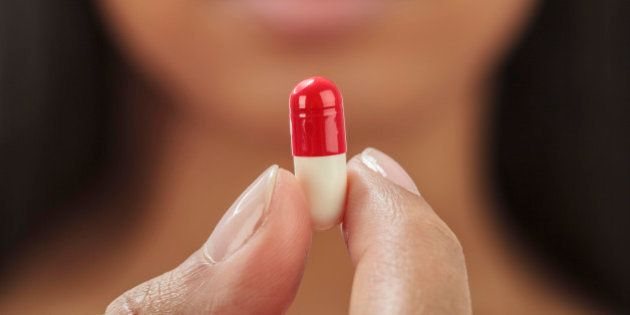 Close up of mixed race woman holding medication