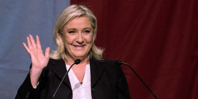 TOPSHOT - The president of the French far-right Front National party Marine Le Pen reacts after the announcement...