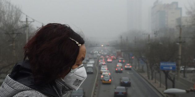 A woman wears a face mask on a heavily polluted day in Beijing on December 26, 2015. Thick smog continued...