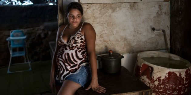 Leydiane da Silva, who's eight months pregnant, rests next to a water storage container, a potential...
