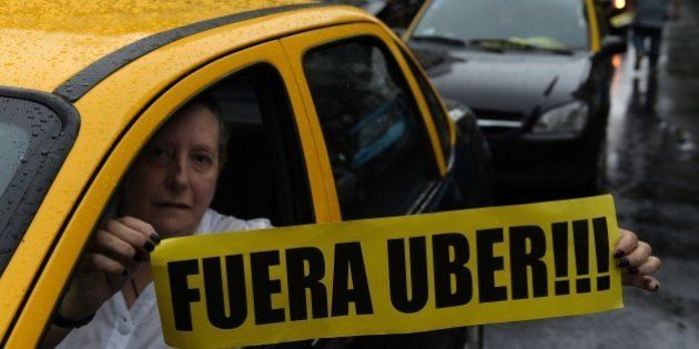 A taxi driver holds a banner reading in Spanish 'Get out Uber' while cabs block Callao avenue, during...