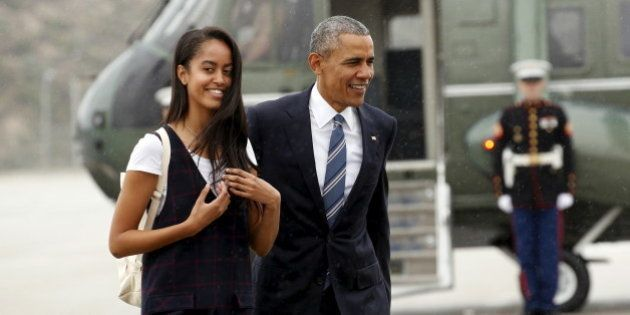 U.S. President Barack Obama and his daughter Malia walk in the rain from Marine One to board Air Force...