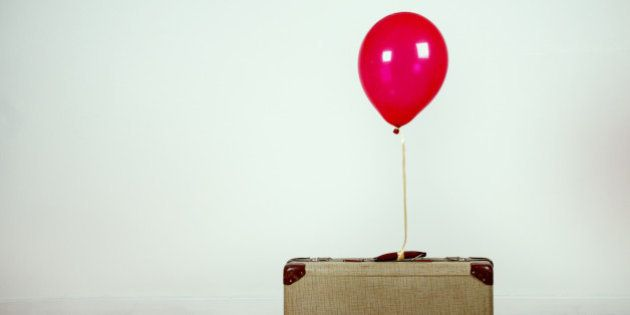 Red helium ballon tied to an old