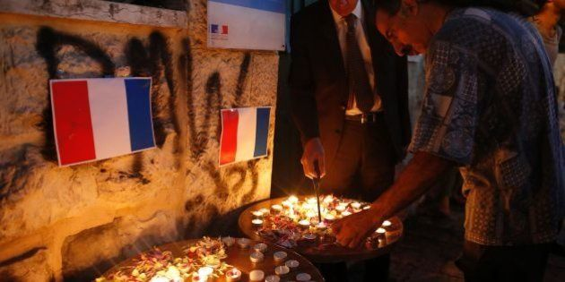 French Consul General Herve Magro (L) lights a candle during a vigil in tribute to the victims of the...