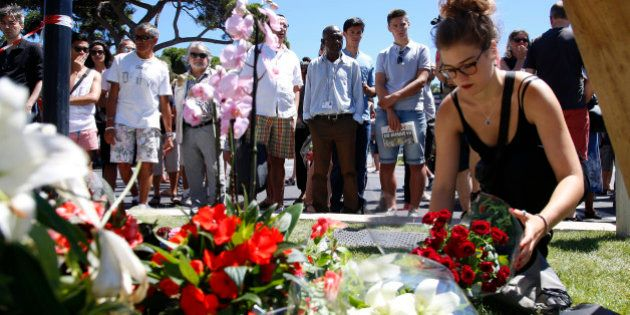 A woman places a bouquet of flowers as people pay tribute near the scene where a truck ran into a crowd...