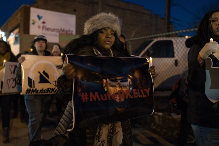 "An activist holds a ""Mute R. Kelly"" sign in Chicago."